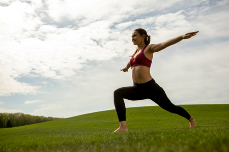 Smiling fit woman is exercising on lawn. She is training balance and flexibility while standing in lunge and stretching arms to sides. Work out outdoors for health concept
