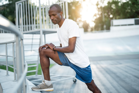 Portrait of positive man stretching body while doing exercise on open air. Concentrating on training concept Banco de Imagens