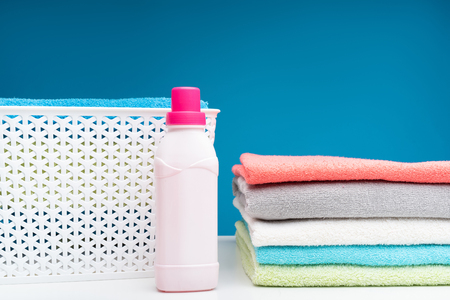 Close up of white board with softened colorful bath linens folded in pile. Plastic clothesbasket and bottle of pink softener are lying aside