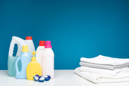 All you need is wash. Washing capsules, liquids and soap standing on one side of white table. Piled laundry lying nearby