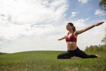 Cheerful lady is enjoying flexibility exercises in park. She is sitting on one leg and straighten arms in sides demonstrating flying. Copy space in left side