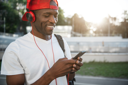 Positive male athlete listening music while typing in mobile. He standing outdoor. Copy space