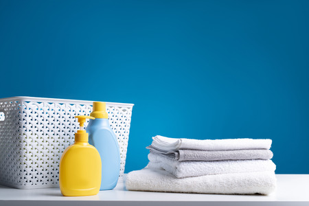 Close up of clean bath towels lying on white table by clothesbasket and detergents. Washing is easy with properly selected means
