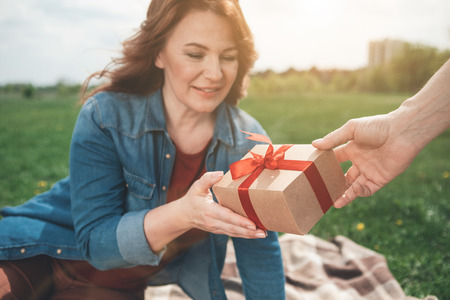 It is for you. Surprised lady is receiving present from her husband. She is looking at it and smiling while relaxing on meadow. Focus on  wrapped box with ribbon in male hand