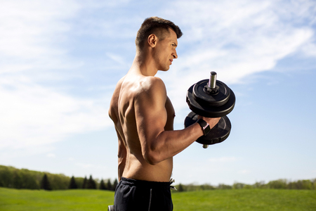 Strenuous guy is exercising with dumbbells among green environment. He is standing on grass and raising forearm for biceps. He is wearing smartwatch and looking forward with tension