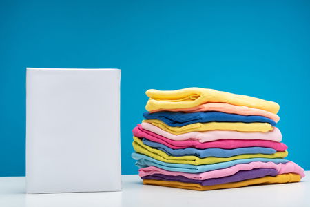 Close up of packet of washing powder put on white board. Pile of fresh colorful garments is folded nearby 版權商用圖片