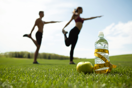 Focus on bottle of water with centimeter band and apple on grass. Sporty couple is doing stretching exercises together on lawn. They are standing on one foot and bending other while keeping balance