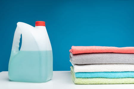 Close up of cotton towels folded in pile. Big bottle of blue laundry detergent is lying aside on clean white board Stock Photo