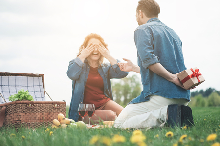 I have surprise for you. Cheerful man is keeping a present box behind his back. Woman is closing her eyes by hands and laughing. They are sitting on meadow while having picnic Foto de archivo - 103905664
