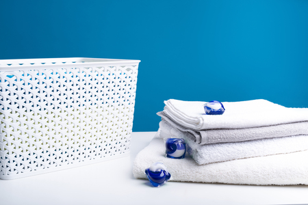 Close up of wicker clothesbasket standing on table. Washing capsules are scattered on clean bath towels. Even the most stubborn stains will come off Stock fotó