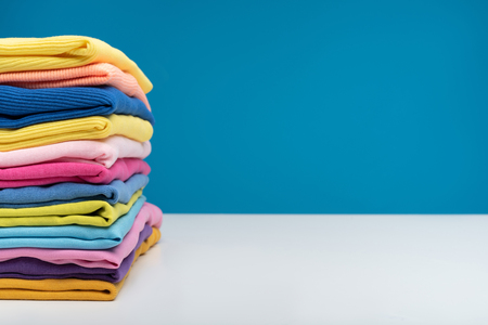 Close up of pile of folded colorful t-shirts after laundry. They are stacked neatly in heap. Copy space in right side Banco de Imagens