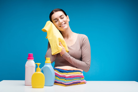 Smiling housewife standing at table and holding yellow t-shirt in hands. She is touching it with cheek and closed eyes in content. Bottles of washing detergents are aside. Copy space in right side