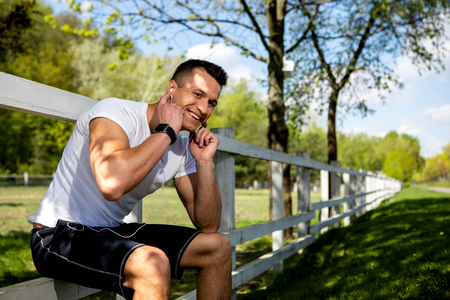 Grinning male is sitting on fence of pasture and enjoying audios. He is touching headphones with fingers and wearing smartwatch. Copy space in right side Reklamní fotografie - 103905844