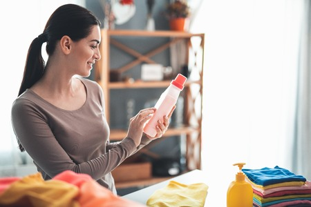 Profile of happy housewife standing at table and holding bottle of detergent in hands. She is reading instructions for use on washing liquid jar. Pile of folded clothes and soap standing aside Stockfoto