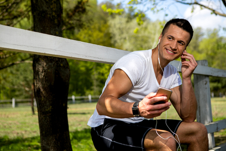 Smiling guy is listening to music on phone while sitting on fence. He is having nice time in nature near green pasture during warm sunny day. Male is wearing smartwatch and looking away with joy
