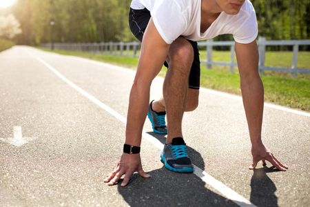 Athletic man is using smartwatch while preparing for sprint on sunny road. He is staying in crouch start with hands touching asphalt. Male is having cardio exercises in open air concept