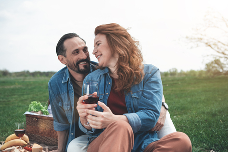 I love you. Cheerful middle-aged woman is looking at her husband with fondness and smiling. Man is embracing his wife while relaxing on meadow