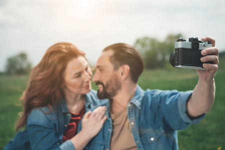Affectionate married couple is using camera while resting on the grassland. They are looking at each other with love and hugging. Focus on digital device Stok Fotoğraf