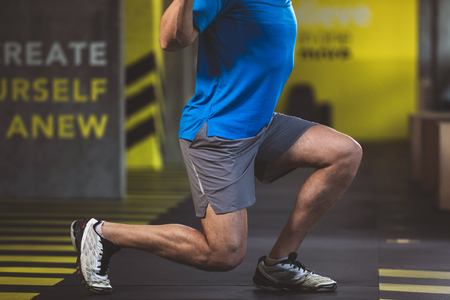 Close up male athlete legs making exercise in fitness center. Sport concept