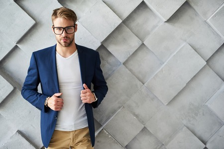 Waist up portrait of confident young businessman standing and touching rims of coat. He is looking forward with certitude. Copy space in right side