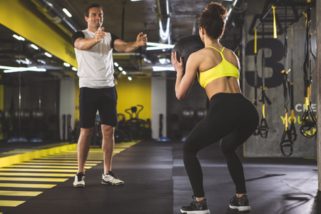 Give it to me. Full length girl holding ball while doing squats. Glad man gesticulating hands while locating opposite her Banco de Imagens