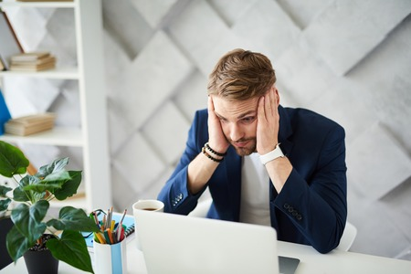 Oh my God. Confused businessman working on project at computer. He is holding head with hand and looking at screen in bewildering Stockfoto