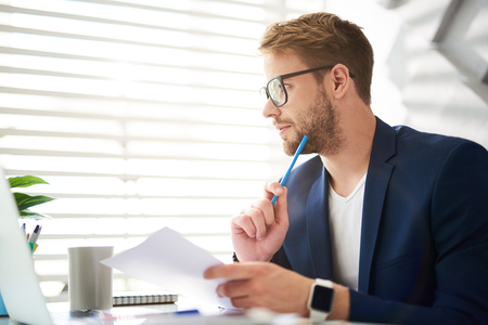 Profile of handsome young male sitting at table and holding papers and blue pencil in hands. He is looking sideways absorbed in personal consideration of business ideas