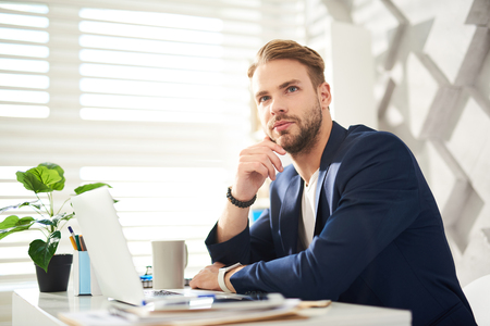 Great idea. Waist up portrait of pensive businessman sitting at desktop with laptop. He is touching chin with hand in consideration of new conceptions