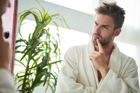 Waist up portrait of pensive male reflection in mirror. He is standing in bathrobe and touching mouth by finger in consideration Stock fotó