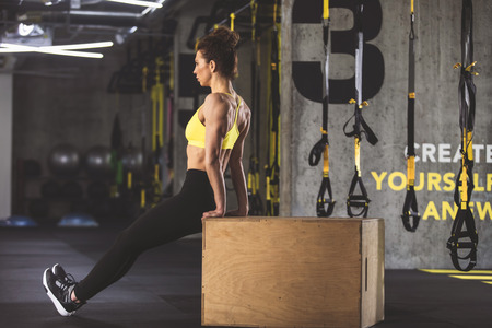 Full length side view orderly girl working out with box in fitness center Stock Photo