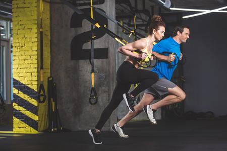 Widok z boku na całej długości wychodzący mężczyzna i skoncentrowana dziewczyna robi ćwiczenia z funkcjonalnymi pętlami. Siedzą w siłowni