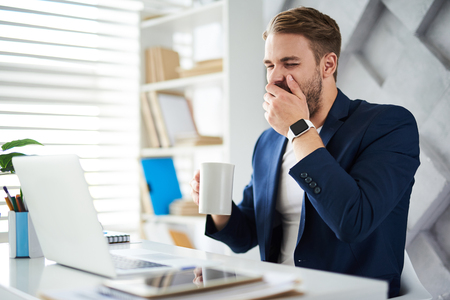 Sleepy morning. Side view of male holding cup of coffee and yawning. He is covering mouth with hand sitting at desktop with computer