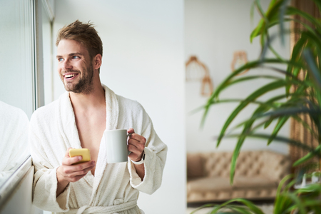 Waist up portrait of smiling man drinking coffee by window. He is wearing white bathrobe and holding mobile while looking sideways with pleasure and joy Stock Photo