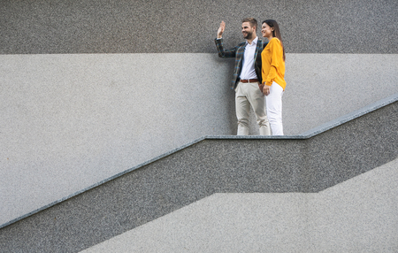 Hello. Excited young businessman is waving hand to his colleague while standing on staircase outdoor. Woman is also smiling