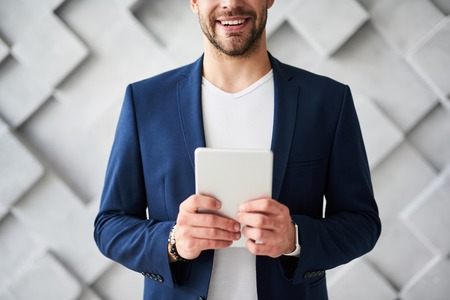 Male carrying tablet in hands. He is standing and chatting online with friends and colleagues with ease and content