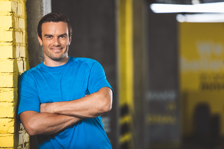 Portrait of cheerful man leaning against wall while locating in fitness center