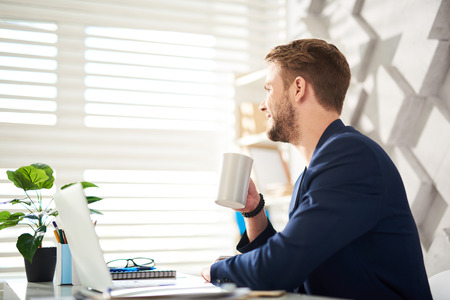 Profile of happy man enjoying morning at work. He is sitting at table and drinking coffee while looking at window with delight