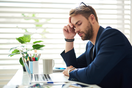 Side view profile of exhausted businessman sitting at laptop during working day. He leaning at hand with his eyes closed feeling drained and sleepy