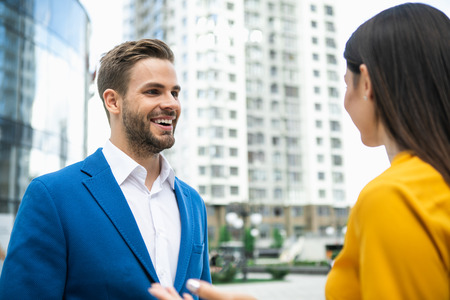 Portrait of excited businessman listening to his colleague with interest. He is standing on street and laughing