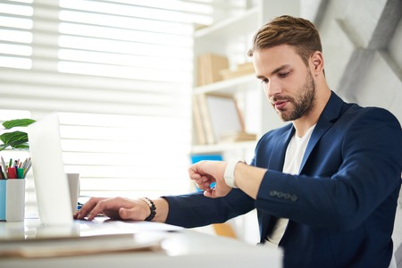 Have to go. Side view of occupied businessman sitting at table and looking at watch. He is working in office with concentration Stock Photo