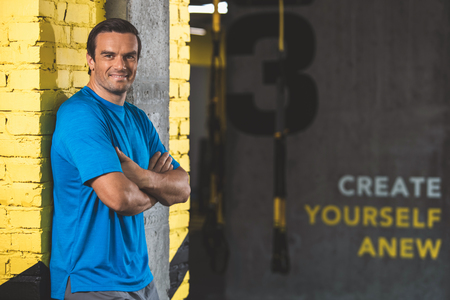 Create yourself anew. Portrait of happy male athlete with crossed arms situating in gym