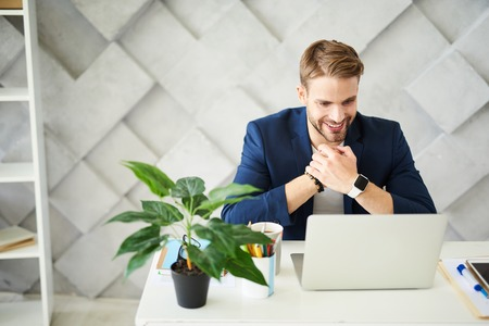 Delighted businessman sitting at neatly organized table with smile. He is rubbing hands with joy looking at laptop screen