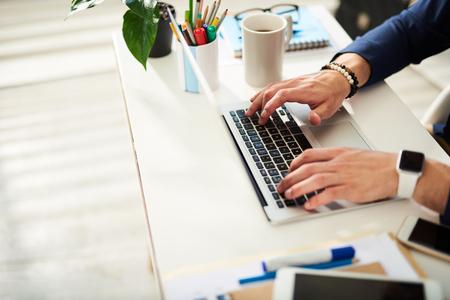 Close up van mannelijke handen typen op laptop. De mens zit en drukt computertrefwoorden in. Koffiemok en een heleboel kleurrijke markeringen en pennen zijn opzij Stockfoto