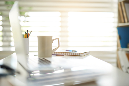 Close up focus on white cup with hot drink standing on desktop. Notebook and colorful pens and pencils are lying aside. Window is on background
