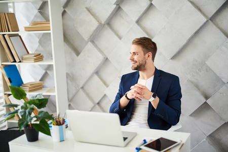 Profile of smiling man sitting at table and looking sideways. He is distracted on window view being joyful and content Stock Photo