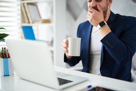 Best way to start morning. Male holding coffee mug at table. Drowsy man is sitting at laptop and covering mouth with hand while yawning Stock Photo