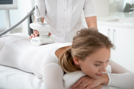 Woman hand making treatment procedure with gadget for young smiling female client in spa center Stock Photo