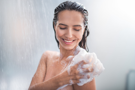 Portrait of happy girl taking shower with gel. She washing with puff