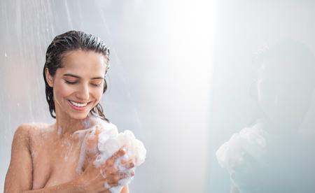 Retrato de mujer radiante frotando el cuerpo con espuma mientras está de pie bajo el vapor de agua. Copia espacio