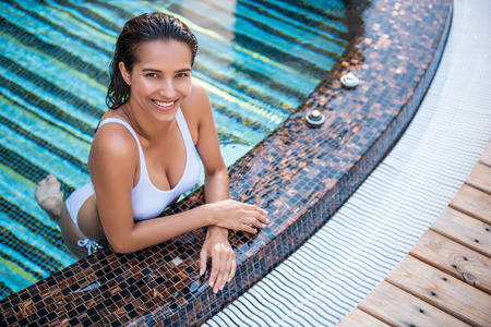 Portrait of happy woman swimming in modern pool while looking at camera. She leaning against side of it